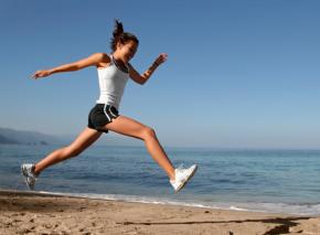 Happy woman running on the beach